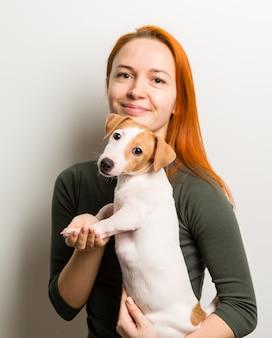 Mujer con pequeño terrier de Russel del enchufe
