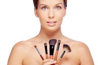 Mujer con pinceles de maquillaje