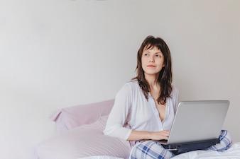 Mujer con portátil pensando