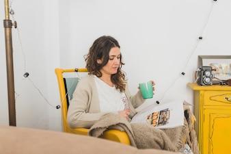 Mujer con taza en la mano leyendo una revista