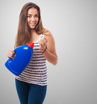 Mujer con un bote de detergente azul