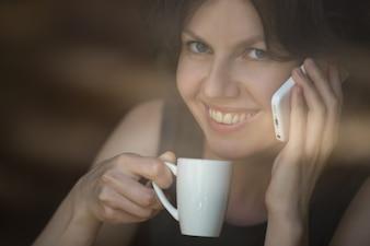 Mujer con un café y hablando por teléfono