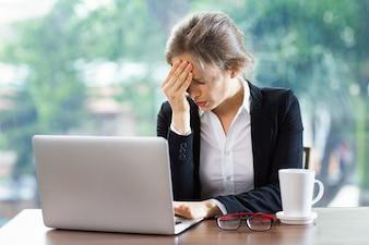 Mujer con un fuerte dolor de cabeza con un portátil y un café