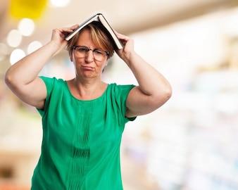 Mujer con un libro encima de su cabeza