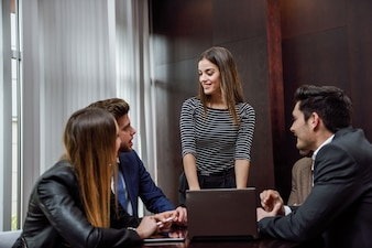 Mujer con un portátil y compañeros de trabajo alrededor