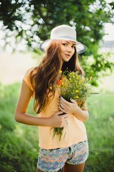 Mujer con un sombrero sujetando flores