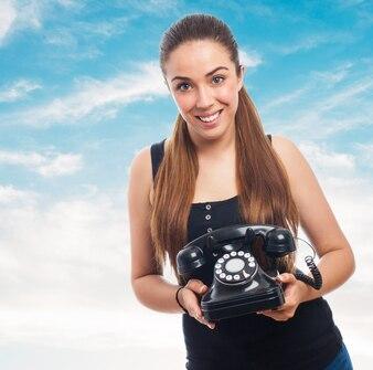 Mujer con un teléfono antiguo en la mano