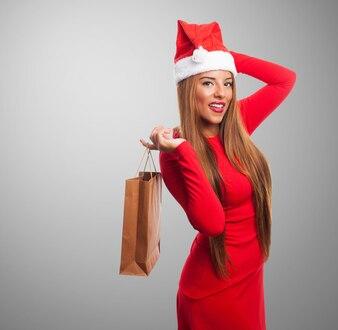 Mujer con una bolsa de la compra  y un sombrero de papa noel