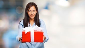 Mujer con una camiseta azul con un regalo rojo