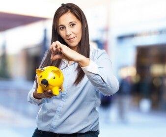 Mujer con una hucha de cerdo amarilla