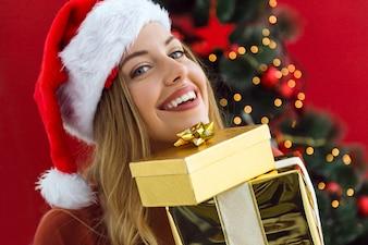 Mujer con una montaña de regalos de colores en sus manos