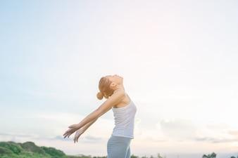 Mujer concentrada estirando sus brazos con el cielo de fondo