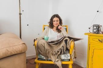Mujer concentrada leyendo el periódico sentada en una silla