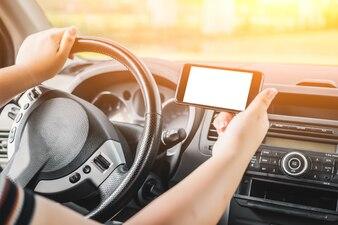 Mujer conduciendo mientras sujeta un móvil en posición horizontal