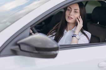 Mujer conduciendo un coche mientras habla por teléfono