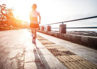 Mujer corriendo hacia el sol