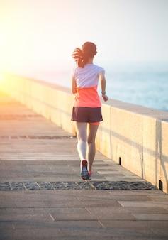 Mujer corriendo por el paseo marítimo
