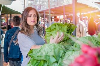 Mujer de compra de frutas y hortalizas en el mercado local de alimentos. Puesto de mercado con variedad de vegetales orgánicos. Retrato de mujer joven hermosa que elige verduras de hoja verde