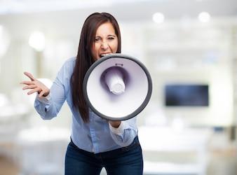 Mujer de negocios agobiada utilizando un altavoz con el fondo borroso