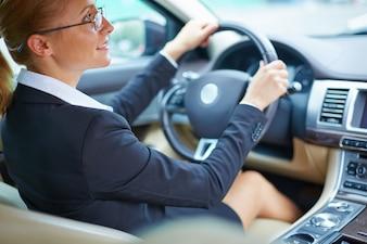Mujer de negocios bien vestida conduciendo