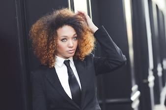 Mujer de negocios bonita tacando su pelo