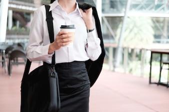 Mujer de negocios caminando bebiendo café.