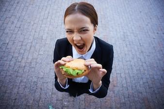 Mujer de negocios con una hamburguesa
