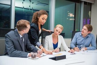 Mujer de negocios enseñando un documento a unos compañeros