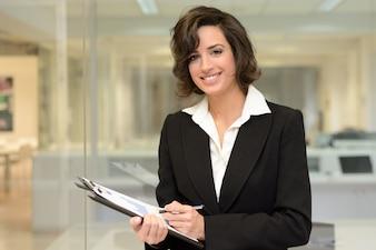 Mujer de negocios feliz sosteniendo un bolígrafo y un portapapeles