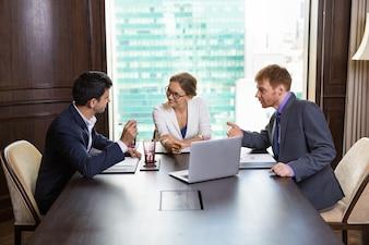 Mujer de negocios hablando con dos hombres de negocios