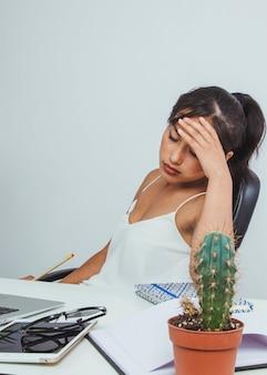 Mujer de negocios joven con dolor de cabeza en el trabajo