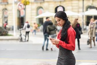 Mujer de negocios joven escribiendo un mensaje en la calle