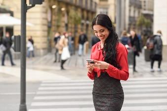 Mujer de negocios morena riéndose con su móvil