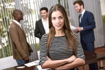 Mujer de negocios segura con sus compañeros de trabajo