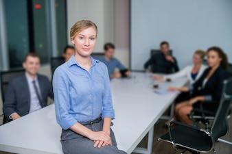 Mujer de negocios sentada en una mesa con trabajadores detrás