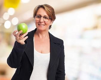 Mujer de negocios sonriendo con una manzana