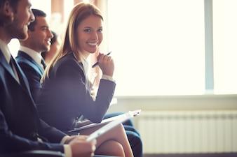 Mujer de negocios sonriente con un bolígrafo en una conferencia