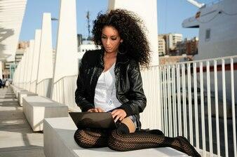 Mujer de pelo rizado trabajando con portátil al aire libre