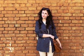 Mujer de pie con pared de ladrillos de fondo