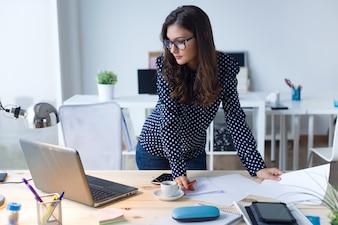 Mujer de pie mirando su ordenador portátil