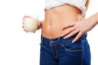 Mujer de vientre plano con vaso de leche