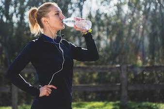 Mujer deportista bebiendo agua al aire libre