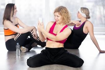 Mujer deportiva con teléfono inteligente en el descanso en la clase de fitness