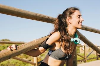 Mujer deportiva estirando brazos en valla vista de cerca