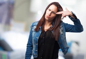 Mujer disparándose a la cabeza con los dedos