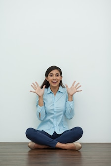 Mujer divertida se sienta en suelo y que muestra las palmas