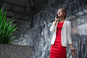 Mujer elegante Contenido joven habla en el teléfono