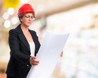Mujer elegante examinando planos
