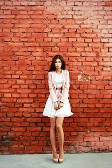 Mujer elegante posando con pared de ladrillos de fondo