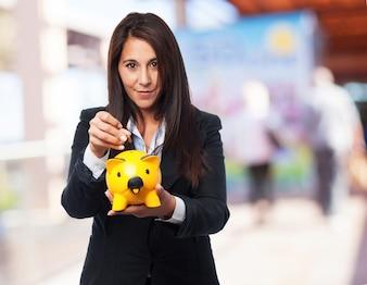 Mujer elegante sonriendo mientras echa una moneda en una hucha amarilla